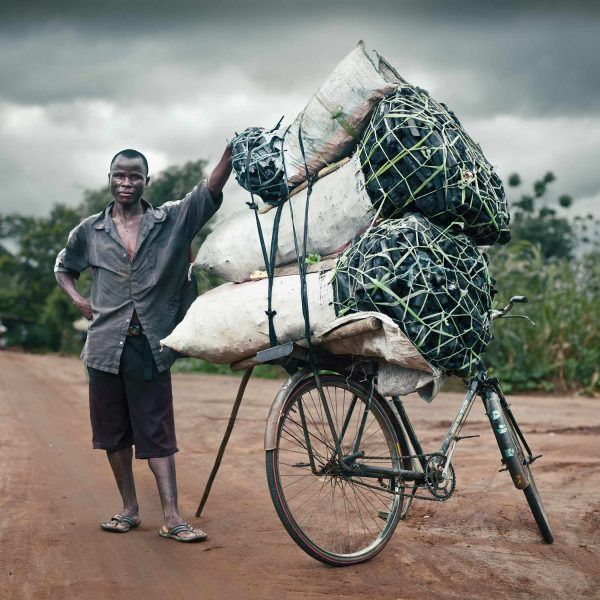 stylish location portrait of a charcoal seller with his bike in rural Malawi by stillvision photography